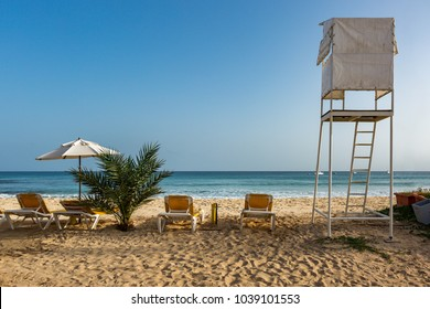 Sunbeds and umbrella next to lifeguard stand on the beach in Santa Maria, Sal, Cape Verde, Cabo Verde