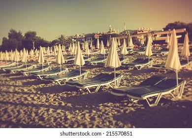 Sunbeds and umbrella on sea beach. Alanya, Turkey, Mediterranean sea. Filtered image:cross processed vintage effect.