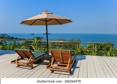 Sunbeds and umbrella overlooking the sea and tropical islands. Taken in Thailand.