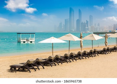 Sunbeds and umbrellas at the beach of luxury hotel in Abu Dhabi in a summer day, United Arab Emirates