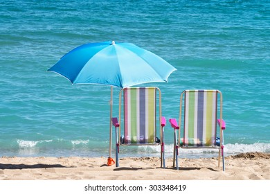 sunbeds and umbrellas in front of the sea horizontal