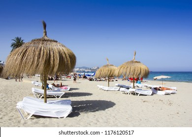 Sunbeds and umbrellas on a beautiful beach in Ibiza, Spain.