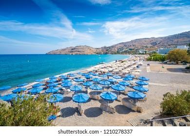 Sunbeds and umbrellas on Vlycha beach near hotel resort (Rhodes, Greece)