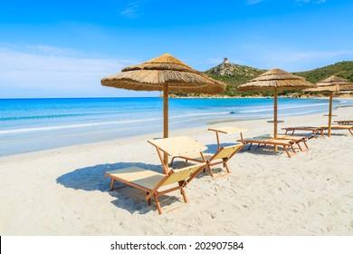Sunbeds with umbrellas on white sand beach, Porto Giunco bay, Sardinia island, Italy