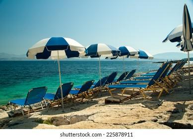 Sunbeds and umbrellas (parasols) on the beach in Corfu Island, Greece