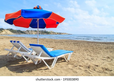 Sunbeds under umbrella on the sandy beach