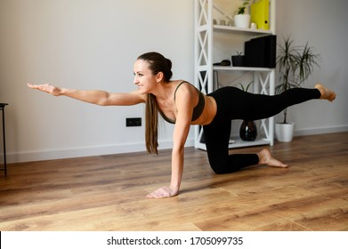Sunbirds asana, pose in yoga. Young positive woman is practicing yoga at home. Healthy lifestyle concept