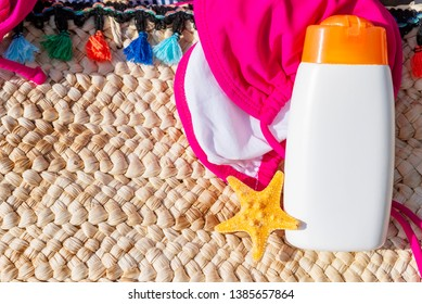 Sunblock lotion bottle with bikini and starfish on floor. Summer travel concept background.