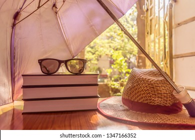 Sunburn risk concept protect your skin from temperatures, Umbrella protecting beautiful woman things. Books sunglasses and a straw hat. Summer holiday concept with copy space room for text.