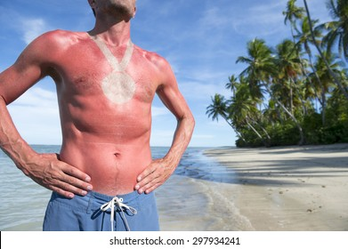 Sunburned athlete standing with outline of medal on empty Brazilian beach