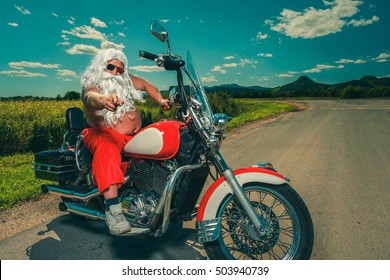 Sunburned Santa biker riding motorcycle on summer vacations