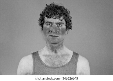 Sunburned sweaty man looks very unhappy in portrait