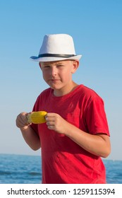 sunburnt boy in white cap and red t-shirt eats boiled corn on the seashore