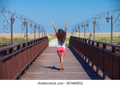 the sunburnt girl stands on a bridge