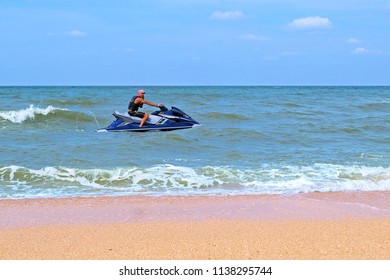 Sunburnt man talking by phone sitting on personal watercraft in sea near empty sandy beach. Sunny day, horizon line.