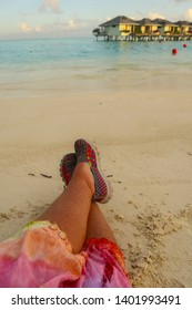 A sunburnt womans legs resting after a long hot Summers Day beside the Indian Ocean in the Maldives with over the water bungalows in the background
