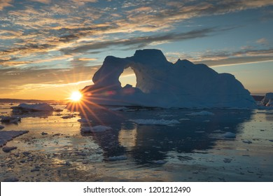 Sunburst behind a massive iceberg with a hole in it during the midnight sun season. Disko bay, Greenland.