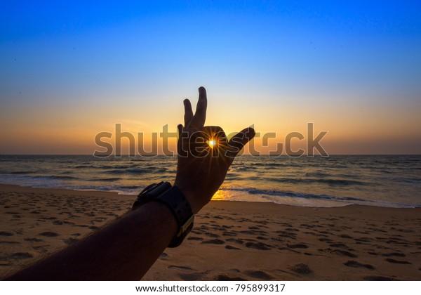 sunburst-sunset-through-human-hands-600w