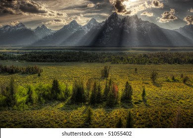 Sunburst through clouds at sunset over Tetons mountain range, Grand Teton National Park