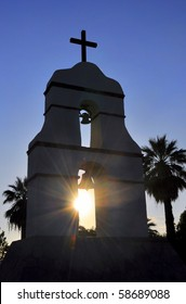 Sunburst through silhouetted mission bell tower.