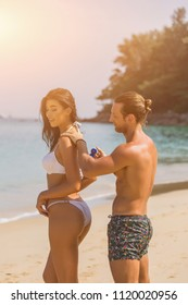 Suncare couple on a summer beach vacation have good skincare with high spf sunblock. Couple applying suncream. Handsome man putting sun tan lotion on his girlfriend at the beach. Toned