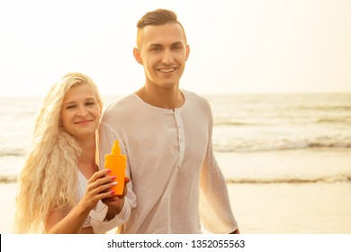 Suncare couple on a summer beach vacation have good skincare with high spf sunblock suncream. Handsome man sun tan lotion on his girlfriend at the beach.