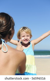 Suncare on the beach: Mother applying suncream to her happy child