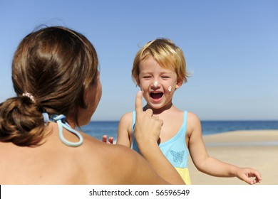 Suncare on the beach: Mother applying sunscream to her happy child