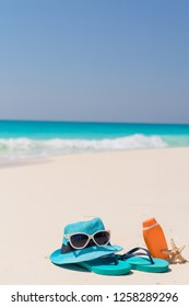 Suncream bottles, goggles, starfish, hat and sunglasses on white sand beach background ocean