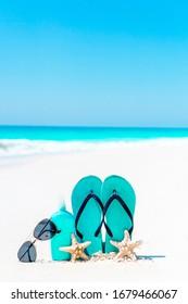 Suncream bottles, goggles, starfish, hat and sunglasses on white sand beach background ocean