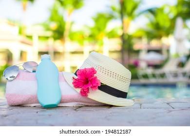 Suncream, hat, sunglasses, flower and tower near swimming pool