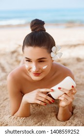 Suncream. Suntan Lotion Beautiful Woman Applying on beautifu on Face. Sunscreen Solar Cream. Skin care. Sun protection.The Girl Uses  Moisturizer Sunblock
