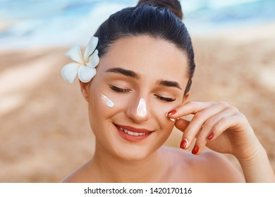 Suncream. Suntan Lotion Beautiful Woman Applying on beautiful on Face. Sunscreen Solar Cream. Skin care. Sun protection.The Girl Uses  Moisturizer Sunblock