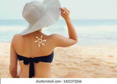 Suncream. Suntan Lotion Beautiful Woman Applying on beautiful on Shoulder In Form Of The Sun. Sunscreen Solar Cream. Skin care. Sun protection.The Girl Uses  Moisturizer Sunblock