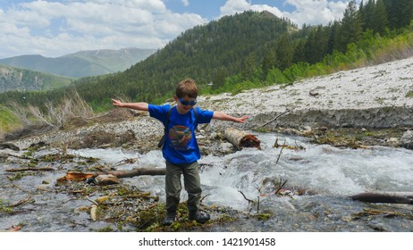 Sundance, Utah / United States - June 11 2019: Happy little boy balances his arms while walking by mountain stream.