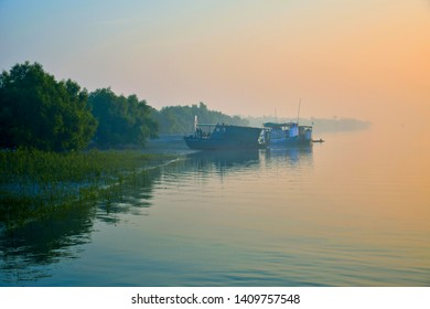 Sundarbans, West Bengal, India – 04/22/2014: Scene of a winter morning, Soft warm lights illuminates still foggy riverbanks. Few tourist motorboats along with a navy patrol boat moored at riverbank
