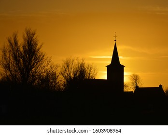 Sundawn behind a church in the Netherlands