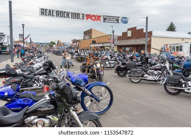 SUNDAY, AUGUST 5, 2018, STURGIS, SD: Motorcyclists roll down Main Street in Sturgis, South Dakota, past hundreds of parked bikes at the annual Sturgis Motorcycle Rally.