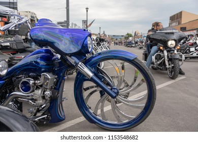 SUNDAY, AUGUST 5, 2018, STURGIS, SD: A motorcyclist and passenger roll down Main Street in Sturgis, South Dakota past a racy, blue custom bike at the annual Sturgis Motorcycle Rally.