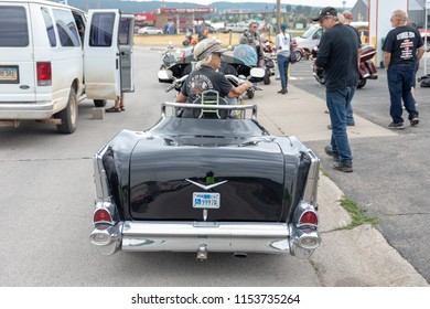 SUNDAY, AUGUST 5, 2018, STURGIS, SD: A woman proudly displays the custom motorcycle her husband built her for their trip to the Sturgis Motorcycle Rally.