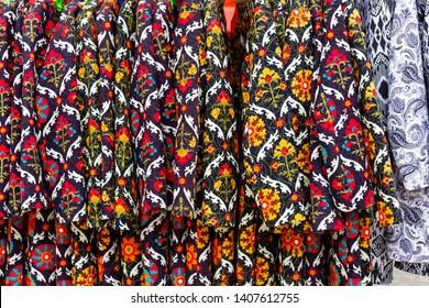 Sunday bazaar in Bukhara, oriental fabrics and handmade clothing.
