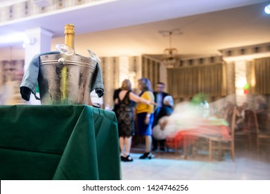 Sunday birthday party in an Italian restaurant. A bottle of champagne is brought to a table and the glasses are set against the blurred background of people dancing in the hall.