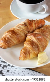 Sunday breakfast. Croissant, coffee and newspaper. Selective focus on croissant. Shot under natural light