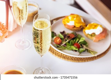 Sunday brunch with prosecco and eggs benedict on white table close-up