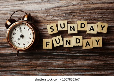 Sunday Funday alphabet letter with alarm clock on wooden background