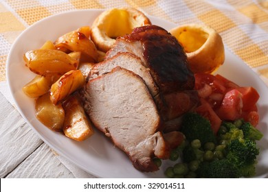 Sunday Roast: baked pork with potatoes, fresh vegetables and Yorkshire pudding on the plate closeup. horizontal