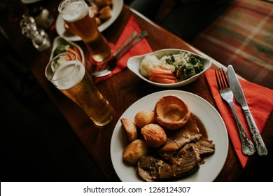 Sunday roast meal with beef, vegetables and beer, with dark light.