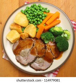 Sunday roast pork dinner with vegetables and gravy.
