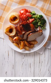 Sunday Roast: pork with potatoes, vegetables and Yorkshire pudding on the table. vertical top view