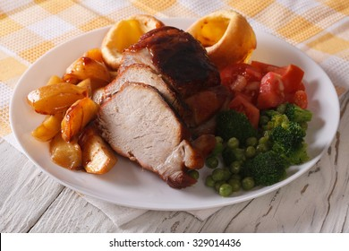 Sunday Roast: pork with potatoes, vegetables and Yorkshire pudding on the plate closeup. horizontal